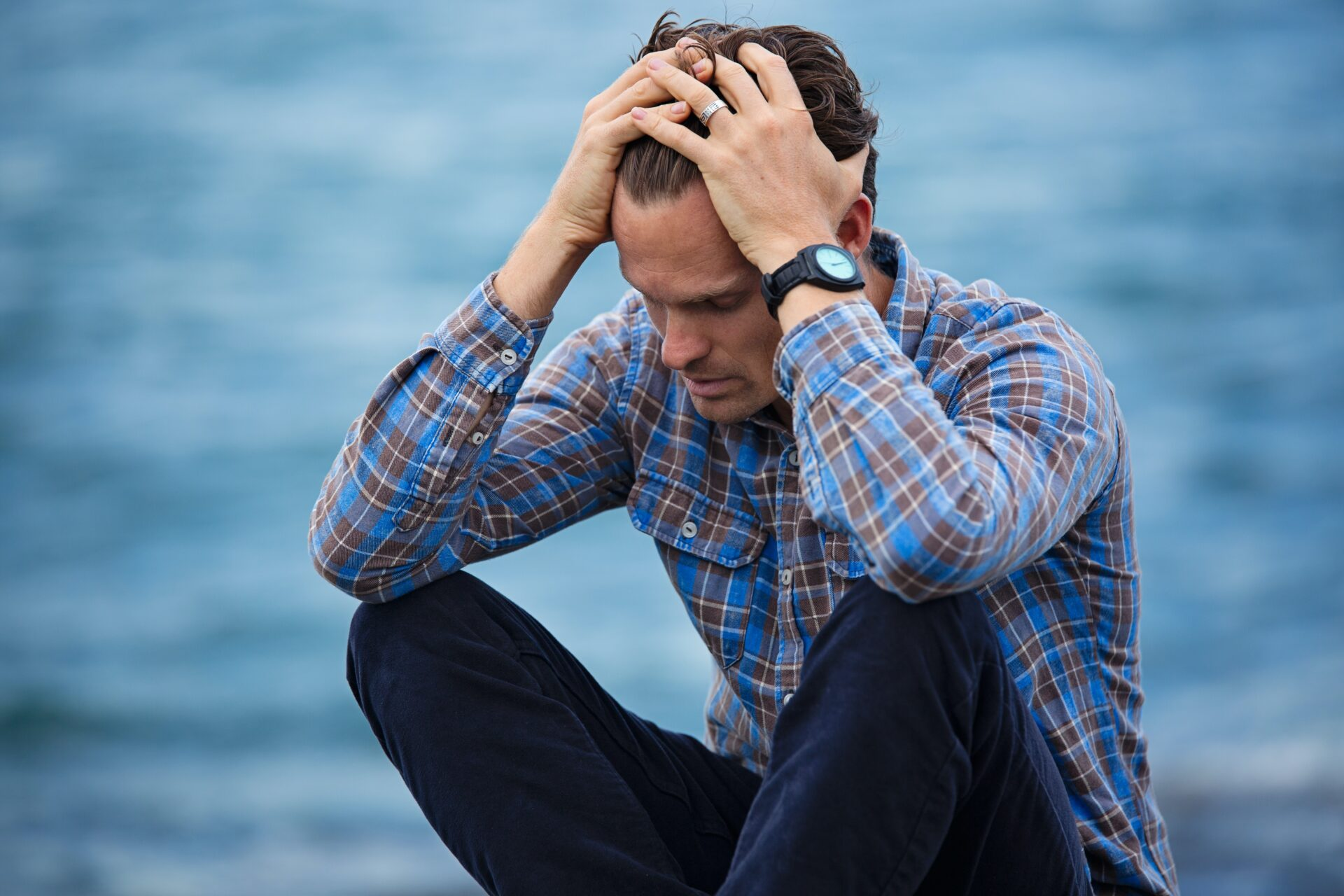 Young man in blue plaid shirt looking overwhelmed
