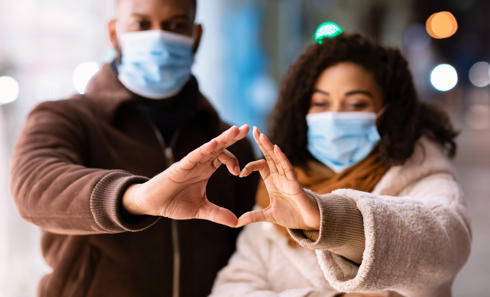 man and woman wearing medical masks making a heart figure with their hands